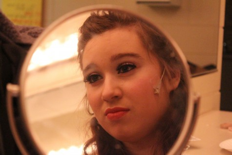 Faith Fuller, who plays Marie, the Fairy Godmother in Cinderella, prepares makeup, costume, and microphone for dress rehearsal.
